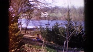 1960: man works the land while river flows behind him, his house Stock Footage