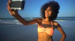 Young happy African American girl in bikini having fun taking selfie  Stock Footage