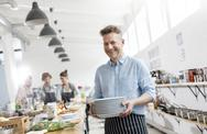 Portrait smiling man in cooking class kitchen Stock Photos