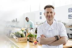 Portrait smiling chef in commercial kitchen Stock Photos