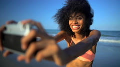 Young happy African American woman in swimsuit having fun taking selfie  Stock Footage
