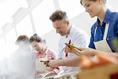 Chef teacher and students peeling asparagus in cooking class kitchen Stock Photos