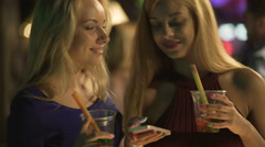 Flirty blonde looking at phone, touching girlfriend's hair gently, nightlife Stock Footage