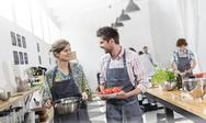 Couple carrying food in cooking class kitchen Stock Photos