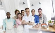 Portrait smiling chef teacher and students in cooking class kitchen Stock Photos
