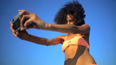 Young smiling African American girl in bikini making video diary online  Stock Footage