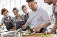 Students watching chef teacher in cooking class kitchen Stock Photos