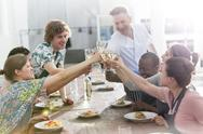 Chef teacher and students toasting wine glasses in cooking class kitchen Stock Photos