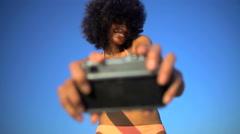 Young happy African American woman in swimwear having fun taking selfie  Stock Footage