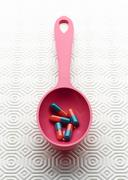 Medical capsules in pink spoon Stock Photos