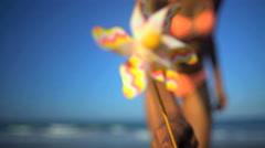 Portrait of beautiful African American girl in bikini relaxing with pinwheel  Stock Footage