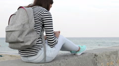 Young woman in striped T-shirt with a backpack sitting on a beach and using a Stock Footage