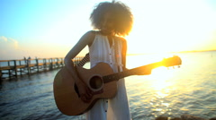 Young attractive African American woman enjoying playing the guitar on her beach Stock Footage
