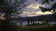Young Women Walk Along Trail And Fence To Enjoy Sunset At Scenic Overlook Stock Footage