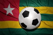 Black and white football ball on the national flag of togo Stock Photos