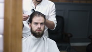 A man looks into a mirror after having his beard groomed at a barber shop. Shot Stock Footage