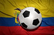 Black and white football ball on the national flag of ecuador Stock Photos