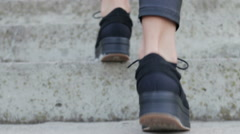 Close-up of female legs in black shoes climbing the stairs Stock Footage