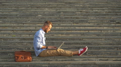 A young busines sitting on stairs working on laptop computer Stock Footage