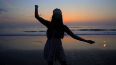 Silhouette of young carefree Indian American woman partying on the beach Stock Footage