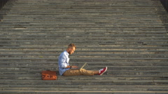 Handsome student sitting on stone steps and using a laptop Stock Footage