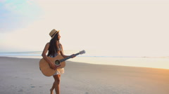 Young happy Asian Indian woman wearing sunhat chilling with the guitar  Stock Footage