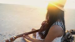 Attractive Asian Indian woman playing the guitar and singing on the beach  Stock Footage