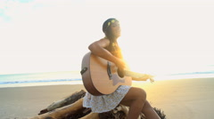 Attractive Asian Indian female playing the guitar and singing on the beach  Stock Footage