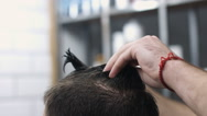 Barber combing back clients hair in barber shop Stock Footage