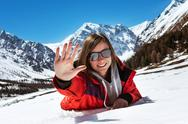 Happy attractive girl lying on the snow on mountains backdrop Stock Photos