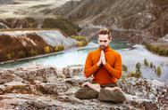 Man meditating in the mountains Stock Photos