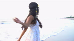 Young carefree Asian Indian female dancing barefoot on the sand on the beach  Stock Footage