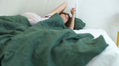 Young beautiful brunette girl in sleepwear waking up in bed. Slow motion. Stock Footage