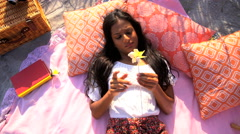 Young slim Asian Indian woman in Retro style sundress relaxing with pinwheel  Stock Footage