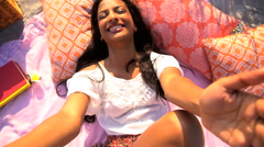 Portrait of happy slim Asian Indian female relaxing with picnic and making video Stock Footage