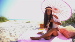 Young attractive Asian Indian girl with parasol enjoying picnic on the beach Stock Footage