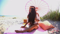 Happy smiling Indian American female chilling with parasol at picnic  Stock Footage