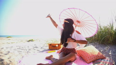 Young happy smiling Asian Indian woman relaxing with parasol at picnic  Stock Footage