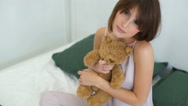 Female model posing with toy bear in bed slow motion Stock Footage