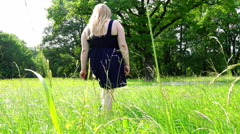 Young girl in a dress walking on summer meadow in the park on the green grass Stock Footage