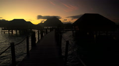 Wooden walkway at sunrise to Overwater luxury Bungalows in tropical lagoon hotel Stock Footage
