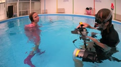 A woman in a pink raincoat and rubber boots posing for underwater photographers Stock Footage