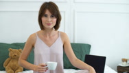 Beautiful woman drinking coffee in bed slow motion Stock Footage