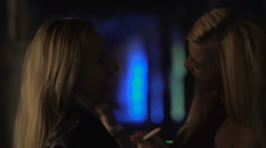 Excited blonde girls dancing at disco, smoking cigarettes, provoking behavior Stock Footage