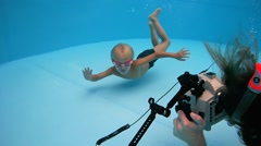 Boy in goggles swimming underwater and posing for underwater photography in the Stock Footage