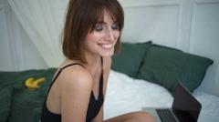 Cheerful young beautiful brunette girl in sleepwear smiling, sitting on bed. Stock Footage