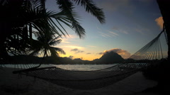 Hammock on the beach at sunrise with Overwater luxury Bungalows in tropical Stock Footage