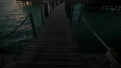 Walkway at sunrise to Overwater luxury Bungalows in tropical lagoon hotel resort Stock Footage