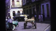 1967: on an town road cart riding middle of the street while jeep over taking it Stock Footage