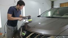 Man on a car wash polishing car with a polish machine Stock Footage